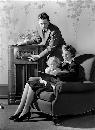 1930s 1940s FAMILY LISTENING TO RADIO WHILE MOTHER READS BOOK TO LITTLE GIRL SEATED IN HER LAP IN ARMCHAIR Stock Photo - Rights-Managed, Code: 846-02796731