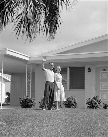 1950s ELDERLY COUPLE STANDING WITH ARMS AROUND EACH OTHER ON MANICURED FRONT LAWN OF RANCH-STYLE Stock Photo - Rights-Managed, Code: 846-02796766