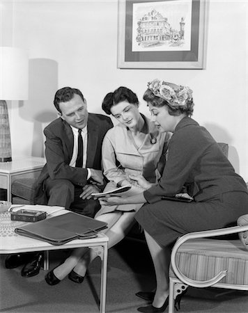 1950s COUPLE MAN WOMAN IN HOME VISITED BY SALESWOMAN SEATED HOLDING SHOWING SALES LITERATURE Stock Photo - Rights-Managed, Code: 846-02796800