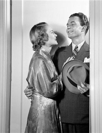 1940s COUPLE IN DOORWAY EMBRACING MAN IN SUIT HOLDING HAT WOMAN IN SATIN PRINT GOWN Stock Photo - Rights-Managed, Code: 846-02796827