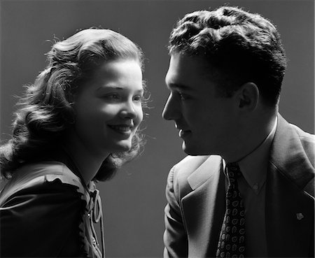 1940s SMILING COUPLE WITH THE KEY LIGHT ON THE WOMAN'S FACE & THE MAN IN SHADOW DRAMATIC ROMANTIC Stock Photo - Rights-Managed, Code: 846-02796859