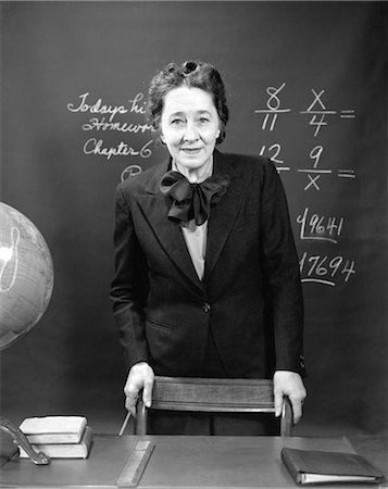 1940s SMILING SCHOOL TEACHER STANDING BEHIND HER DESK & IN FRONT OF THE BLACK BOARD WITH FRACTIONS Stock Photo - Rights-Managed, Code: 846-02796886