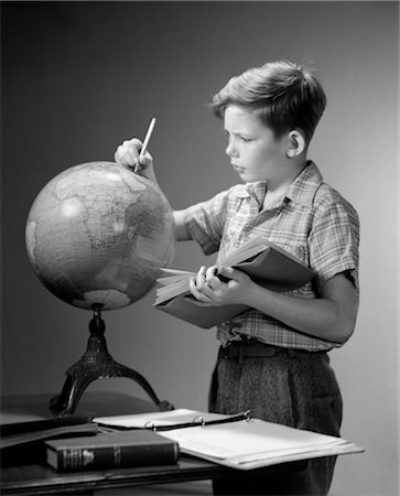 1940s 1950s SERIOUS BOY FINDING LOCATION ON WORLD EARTH GLOBE WITH PENCIL HOLD OPEN BOOK GEOGRAPHY Stock Photo - Rights-Managed, Code: 846-02796908