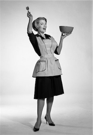 1950s WOMAN IN APRON HOLDING MIXING BOWL AND SPOON EXAGGERATED EXPRESSION Stock Photo - Rights-Managed, Code: 846-02796947
