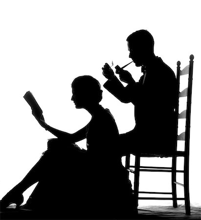 1930s SILHOUETTE OF MAN IN LADDER-BACK CHAIR SMOKING PIPE WITH WOMAN SEATED ON FLOOR IN FRONT OF HIM READING BOOK Stock Photo - Rights-Managed, Code: 846-02796949