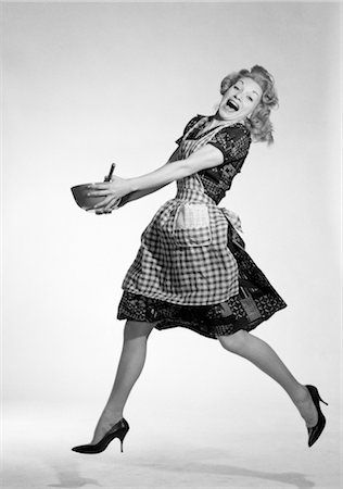 1950s WOMAN IN CHECKERED APRON JUMPING WITH GLEE HOLDING SPOON MIXING BOWL WITH BOTH HANDS BIG SMILE Stock Photo - Rights-Managed, Code: 846-02796950