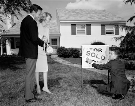 sold sign - 1960s SMILING COUPLE STANDING ON FRONT LAWN OF NEW HOUSE LOOKING DOWN AT REALTOR PUTTING UP SOLD SIGN Stock Photo - Rights-Managed, Code: 846-02797000