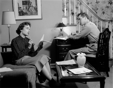 1950s COUPLE IN LIVING ROOM LOOK OVER HOUSEHOLD BILLS FINANCE WOMAN ON COUCH LIST IN HAND MAN SITS AT DESK BY STAIRS Stock Photo - Rights-Managed, Code: 846-02797041