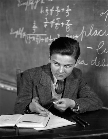 1920s 1930s BOY AT DESK IN CLASSROOM IN FRONT OF BLACKBOARD SHOOTING PAPER WAD WITH RUBBER BAND Stock Photo - Rights-Managed, Code: 846-02797148