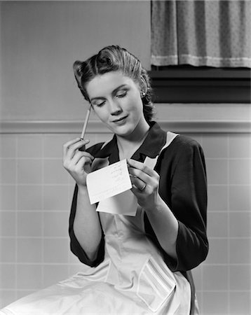 1940s 1950s WOMAN SITTING IN KITCHEN HOLDING SHOPPING LIST Stock Photo - Rights-Managed, Code: 846-02797202