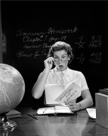 1950s SCHOOL TEACHER AT DESK HAND TO GLASSES EXPRESSION OF SURPRISE OPENING A VALENTINE FOR TEACHER GLOBE BLACKBOARD Stock Photo - Rights-Managed, Code: 846-02797216