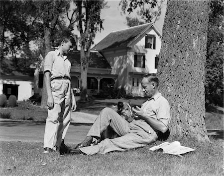 sitting under tree - 1940s FATHER AND DOG SITTING UNDER TREE TEENAGE SON STANDING FRONT YARD HOUSES STREET COMMUNITY Stock Photo - Rights-Managed, Code: 846-02797222