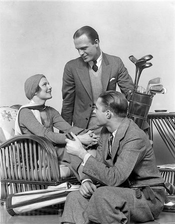 1930s TWO MEN ONE WOMAN GOLF CLUBS AND BAG SMILING TALKING SITTING BAMBOO CHAIR MAN SMOKING PIPE Stock Photo - Rights-Managed, Code: 846-02797242