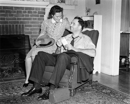 1940s SMILING MAN SITTING IN CHAIR HOLDING PAY ENVELOPE WHILE WIFE SITS ON ARM OF CHAIR HOLDING HIS HAT LUNCH BOX ORIENTAL RUG Stock Photo - Rights-Managed, Code: 846-02797254
