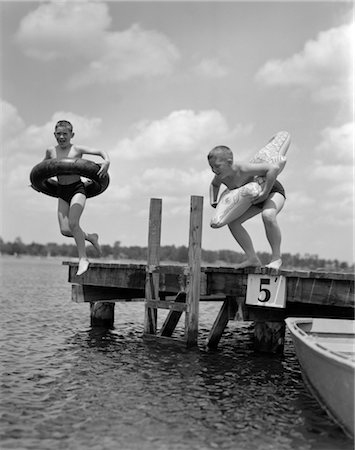 1940s 1950s TWO BOYS WEARING INFLATABLE INNER TUBES ABOUT TO JUMP IN LAKE OFF PIER Stock Photo - Rights-Managed, Code: 846-02797266