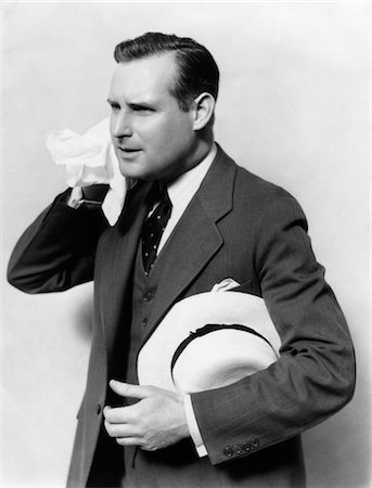 sweaty businessman - 1930s MAN IN SUIT HOLDING HAT WIPING FACE WITH HANDKERCHIEF Stock Photo - Rights-Managed, Code: 846-02797275