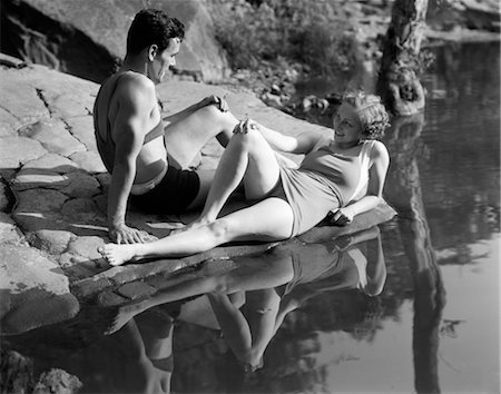 1930s COUPLE LYING ON ROCKS NEAR WATER WEARING BATHING SUITS Stock Photo - Rights-Managed, Code: 846-02797327