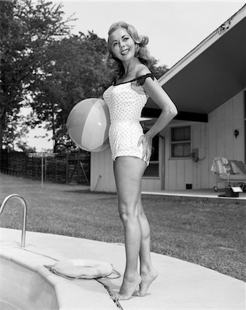 1950s WOMAN HOLDING BEACH BALL STANDING BY IN GROUND SWIMMING POOL WEARING BATHING SUIT Stock Photo - Rights-Managed, Code: 846-02797353