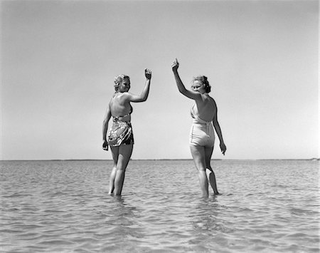 1930s TWO GIRLS STANDING IN WATER WEARING BATHING SUITS LOOKING BACK WAVING Stock Photo - Rights-Managed, Code: 846-02797363