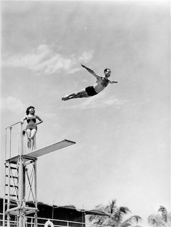 1940s MAN SWAN DIVING OFF HIGH DIVING BOARD WOMAN WATCHING Stock Photo - Rights-Managed, Code: 846-02797379