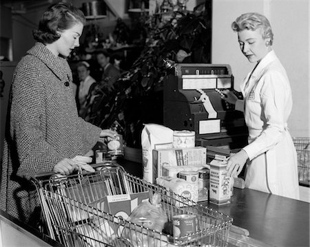 1950s WOMAN AT GROCERY STORE CHECKOUT COUNTER HANDING ITEMS OVER FOR CASHIER TO RING UP ON CASH REGISTER Stock Photo - Rights-Managed, Code: 846-02797386