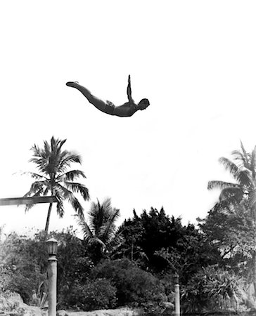 1930s MAN POISED MIDAIR ARMS OUT JUMPING FROM DIVING BOARD INTO POOL Stock Photo - Rights-Managed, Code: 846-02797387