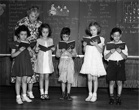 1930s LINE-UP OF 5 ELEMENTARY SCHOOL STUDENTS IN FRONT OF BLACKBOARD READING BOOKS WITH TEACHER LOOKING ON Stock Photo - Rights-Managed, Code: 846-02797403