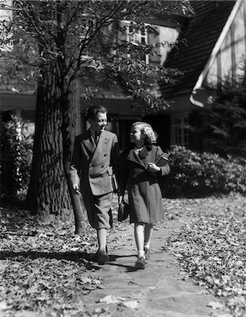 1930s 1940s BOY GIRL WALKING ON SIDEWALK AUTUMN LEAVES CARRYING SCHOOL BOOKS WEAR WOOL COAT BOY Stock Photo - Rights-Managed, Code: 846-02797415