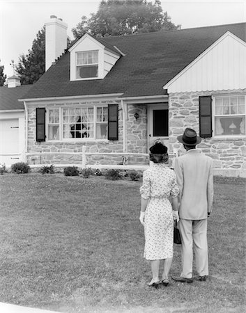 1940s 1950s COUPLE STANDING OUTSIDE LOOKING AT STONE SUBURBAN HOUSE Stock Photo - Rights-Managed, Code: 846-02797413