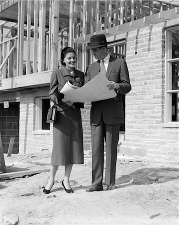 1950s COUPLE LOOKING AT BUILDING PLANS STANDING IN FRONT OF UNFINISHED HOUSE Stock Photo - Rights-Managed, Code: 846-02797422