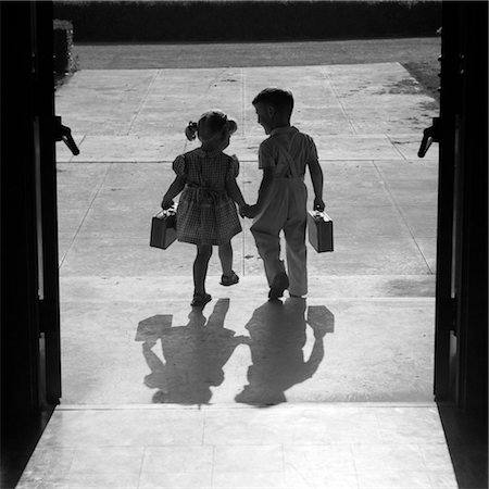 1950s SILHOUETTED BOY GIRL HOLDING HANDS LEAVING SCHOOL DOORS GOING HOME END OF DAY SHADOWS AFTERNOON FRIENDS FRIENDSHIP Stock Photo - Rights-Managed, Code: 846-02797431