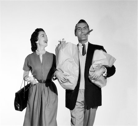 1950s COUPLE WALKING WOMAN SMILING AT MAN CARRYING GROCERY BAGS SMOKING CIGAR Stock Photo - Rights-Managed, Code: 846-02797484