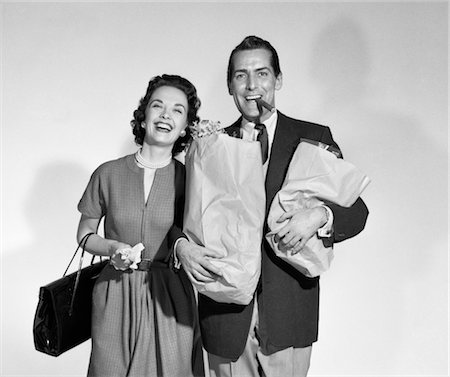 1950s COUPLE SMILING WOMAN MAN CARRYING GROCERY BAGS SMOKING CIGAR SEAMLESS Stock Photo - Rights-Managed, Code: 846-02797485