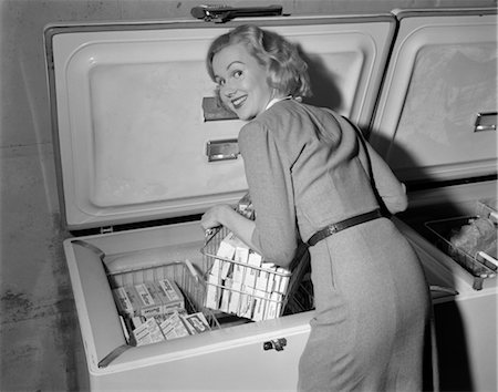 1950s BLOND WOMAN LIFTING WIRE BASKET FOOD ITEMS FROM A DEEP FREEZER LOOKING OVER HER SHOULDER Stock Photo - Rights-Managed, Code: 846-02797487