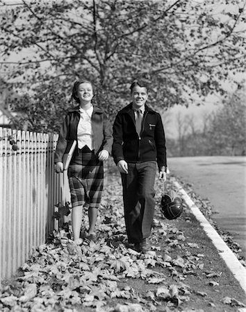 1930s TEEN COUPLE WALKING ON SIDEWALK IN FALL GIRL CARRYING SCHOOLBOOKS BOY CARRYING FOOTBALL AND LEATHER HELMET SMILING OUTDOOR Stock Photo - Rights-Managed, Code: 846-02797517