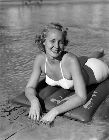1940s SMILING BLOND WOMAN WEARING WHITE TWO PIECE BATHING SUIT LAYING ON INFLATED RAFT Stock Photo - Rights-Managed, Code: 846-02797523