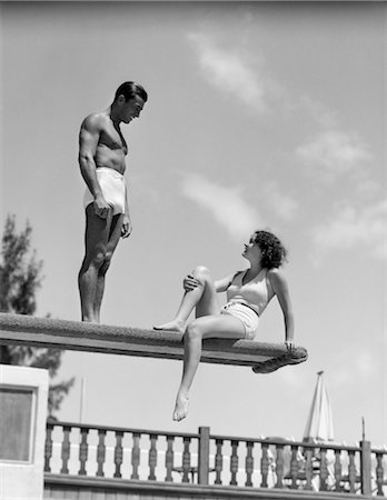 1930s COUPLE BY SWIMMING POOL ON DIVING BOARD TALKING Stock Photo - Rights-Managed, Code: 846-02797542