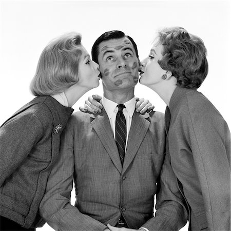 1950s TWO WOMEN KISSING SINGLE MAN ON OPPOSITE CHEEKS HIS FACE COVERED WITH LIPSTICK MARKS Stock Photo - Rights-Managed, Code: 846-02797551