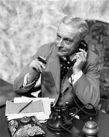 1930s ELDER MAN SITTING AT DESK SMOKING CIGAR TALKING ON TELEPHONE Stock Photo - Rights-Managed, Code: 846-02797616