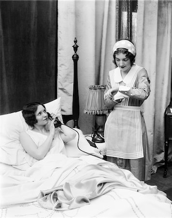 1920s 1930s TWO WOMEN IN BEDROOM MAID LOOKING AT WRIST WATCH OTHER WOMAN IN BED TALKING ON PHONE HAND HELD OVER MOUTHPIECE Stock Photo - Rights-Managed, Code: 846-02797626