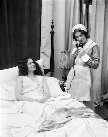 1920s 1930s TWO WOMEN IN BEDROOM ONE DRESSED AS MAID ON TELEPHONE OTHER IN BED SMILING UP AT MAID WINDOW CURTAINS UNIFORM Stock Photo - Rights-Managed, Code: 846-02797627