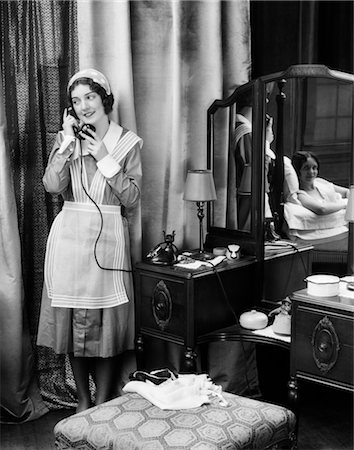 1920s 1930s MAID IN UNIFORM TALKS ON TELEPHONE IN FRONT OF VANITY DRESSING TABLE OTHER WOMAN IS SEEN AS REFLECTION IN MIRROR Stock Photo - Rights-Managed, Code: 846-02797628
