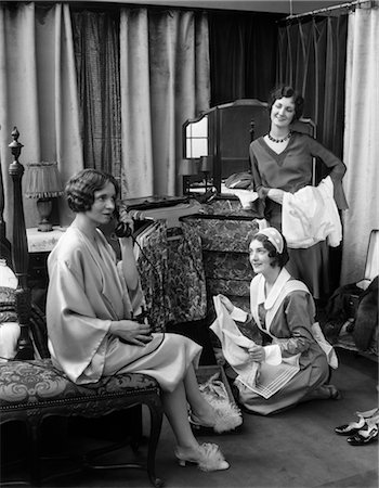 1920s 1930s THREE WOMEN IN BEDROOM ONE IN LINGERIE TALKING TELEPHONE LOOKING MAID PACKING SUITCASES TRUNK MIRROR VANITY TRAVEL Stock Photo - Rights-Managed, Code: 846-02797630