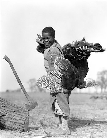 1920s 1930s AFRICAN AMERICAN BOY IN KNICKERS HOLDING A LIVE TURKEY OVER HIS SHOULDER STANDING BY A LOG EMBEDDED WITH AN AX Stock Photo - Rights-Managed, Code: 846-02797647