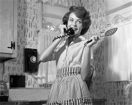 1950s 1960s SMILING WOMAN TALKING WALL TELEPHONE HOLDING SPOON WEARING APRON STANDING IN KITCHEN Stock Photo - Rights-Managed, Code: 846-02797699