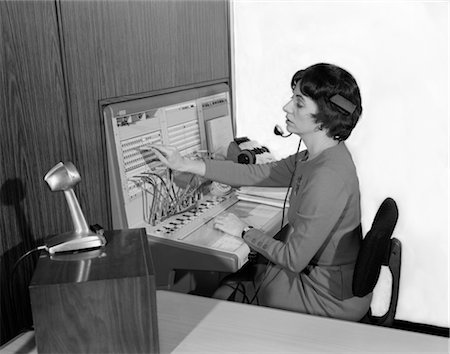 1960s WOMAN OFFICE TELEPHONE SWITCHBOARD OPERATOR WEARING HEADSET TRANSFERRING CALL RECEPTIONIST ANSWERING SERVICE MICROPHONE Stock Photo - Rights-Managed, Code: 846-02797700