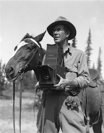 1940s MAN IN FEDORA & JODHPURS STANDING NEXT TO SADDLED HORSE HOLDING GRAFLEX CAMERA Stock Photo - Rights-Managed, Code: 846-02797722