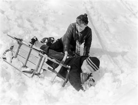 1930s 1940s TWO BOYS LAUGHING IN SNOW JUST FALLEN OFF OF SLED THAT IS TURNED ON ITS SIDE Stock Photo - Rights-Managed, Code: 846-02797741
