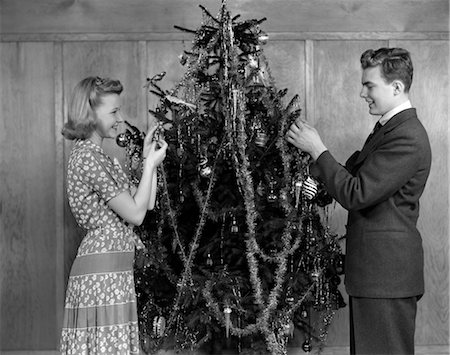 1930s 1940s COUPLE DECORATING CHRISTMAS TREE WITH TINSEL AND ORNAMENTS Stock Photo - Rights-Managed, Code: 846-02797869