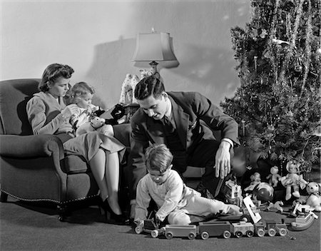 sitting under tree - 1930s 1940s FAMILY AROUND CHRISTMAS TREE BOY PLAYING WITH TRAIN DAD HELPING MOM Stock Photo - Rights-Managed, Code: 846-02797863